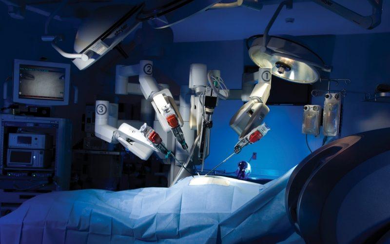 вид операционной с готовыми к выполнению операции и склоненными над пустым операционным столом роботами